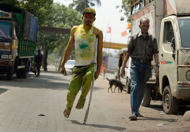 A physically challenged man smeared in coloured powder walks on a road in Mumbai on March 13, 2017. Holi, the festival of colours, is a riotous celebration of the coming of spring and falls on the day after full moon annually in March. (Punit Paranjpe/AFP/Getty Images)