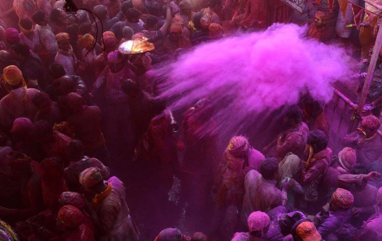"In this photograph taken on March 6, 2017, Indian devotees throw colored powder during celebrations for Lathmar Holi in Barsana on the outskirts of Mathura in the northern Indian state of Uttar Pradesh. Lathmar Holi is a local celebration of the Hindu festival of Holi, usually some days ahead of the actual festival - it translates as 'that Holi in which people hit with sticks"". (STRSTR/AFP/Getty Images)"