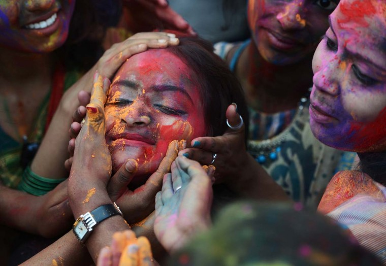 Indian students smear colored powder at an event to celebrate the Hindu festival of Holi in Kolkata on March 7, 2017. Holi, the popular Hindu spring festival of colors is observed in India at the end of the winter season on the last full moon of the lunar month, and will be celebrated on March 13 this year. (DIBYANGSHU SARKAR/AFP/Getty Images)
