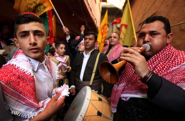 Iraqi Kurds play music as they walk through the town of Akra, 500 km north of Baghdad, on March 20, 2017 as they celebrate the Noruz spring festival. (SAFIN HAMED/AFP/Getty Images)
