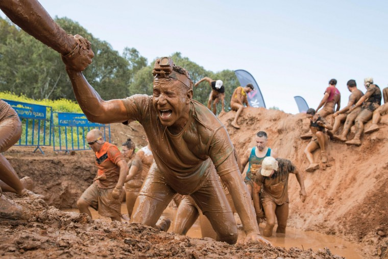 Participants take part in the Mud Day race, a 13km obstacle course, on March 24, 2017 in the Israeli Mediterranean coastal city of Tel Aviv. (Jack Guez/AFP/Getty Images)