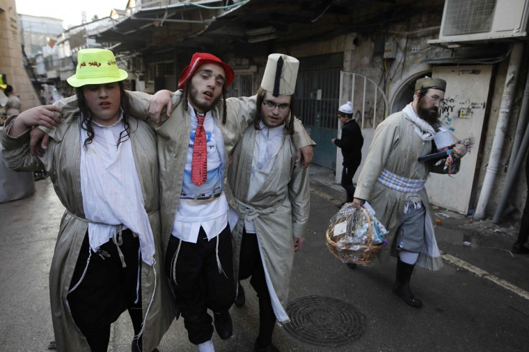 Ultra-Orthodox Jewish men walk in the street after getting drunk in Jerusalem's Mea Shearim ultra-Orthodox neighbourhood on March 13, 2017 during the religious holiday of Purim. The carnival-like Purim holiday is celebrated with parades and costume parties to commemorate the deliverance of the Jewish people from a plot to exterminate them in the ancient Persian Empire 2,500 years ago, as recorded in the Biblical Book of Esther. (AFP PHOTO / MENAHEM KAHANA)