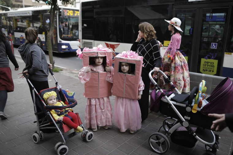 Ultra-Orthodox Jewish children wearing costumes stand on a street in the central Israeli city of Bnei Brak on March 12, 2017 during the feast of Purim. The carnival-like Purim holiday is celebrated with parades and costume parties to commemorate the deliverance of the Jewish people from a plot to exterminate them in the ancient Persian Empire 2,500 years ago, as recorded in the Biblical Book of Esther. (AFP PHOTO / MENAHEM KAHANA)