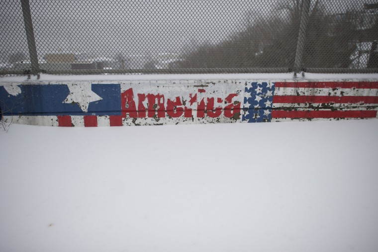"A mural stating ""America"" is partially covered by snow March 14, 2017 in Philadelphia, Pennsylvania. A blizzard is forecast to bring more than a foot of snow and high winds to up to eight states in the Northeast region, as New York and New Jersey are under a state of emergency. School districts across the entire region were closed and thousands of flights were canceled. (Photo by Mark Makela/Getty Images)"