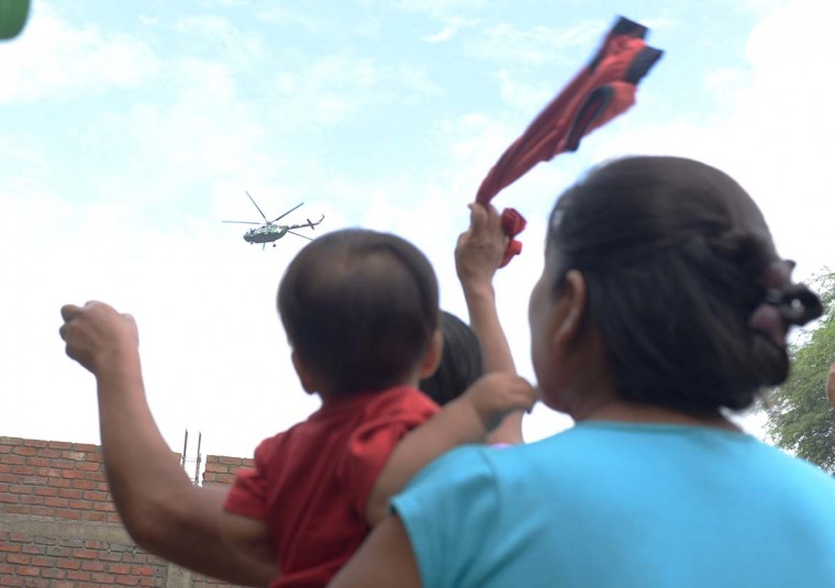Residents wave for assistance to a passing army helicopter in Piura, northern Peru on March 28, 2017. More than 50,000 people have been displaced by flood water in the region of Piura in northern Peru and hundreds of houses have been flooded. Many local residents are being taken to shelters set up by the government, while others refuse to leave their land and prefer to stay on high ground in their communities. (MIGUEL ARREATEGUI,STR/AFP/Getty Images)