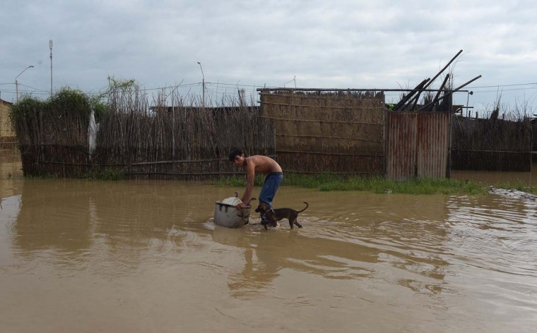 A local resident wades through floodwater with his dog after heavy rains in Piura, northern Peru on March 28, 2017. (MIGUEL ARREATEGUI,STR/AFP/Getty Images)