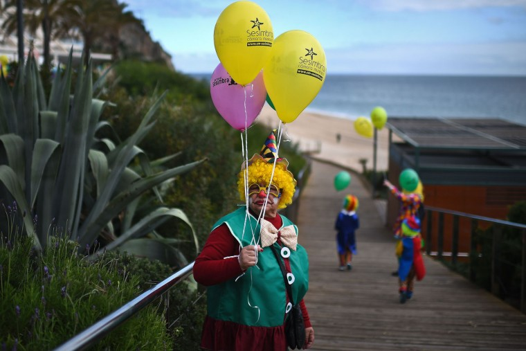 A woman dressed as a clown holds balloons during the Carnival Clown's Parade at Sesimbra village on February 27, 2017. (Patricia de Melo Moreira/AFP/Getty Images)