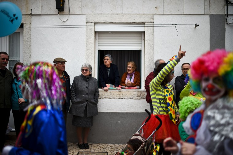 Two women stand at a window watching the Carnival Clown's Parade at Sesimbra village on February 27, 2017. (Patricia de Melo Moreira/AFP/Getty Images)