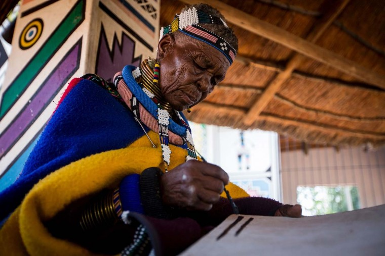 South African artist Esther Mahlangu, 81, paints at her home in Mabhoko Village, Siyabuswa, Mpumalanga on March 6, 2017. Mahlangu recently opened her exhibition at the Melrose Gallery where her series of artwork inspired by Nelson Mandela was unveiled on March 1. The artist has produced six paintings reproduced from drawings created by Mandela in her signature Ndebele style. The exhibition will include previous work by Mahlangu. (GULSHAN KHAN/AFP/Getty Images)