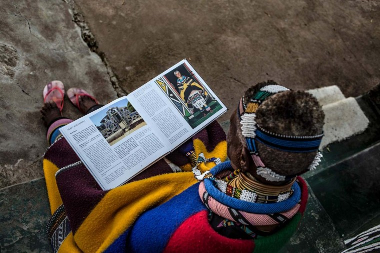 South African artist Esther Mahlangu, 81, read a biography of work at her home in Mabhoko Village, Siyabuswa, Mpumalanga on March 6, 2017. Mahlangu recently opened her exhibition at the Melrose Gallery where her series of artwork inspired by Nelson Mandela was unveiled on March 1. The artist has produced six paintings reproduced from drawings created by Mandela in her signature Ndebele style. The exhibition will include previous work by Mahlangu. (GULSHAN KHAN/AFP/Getty Images)