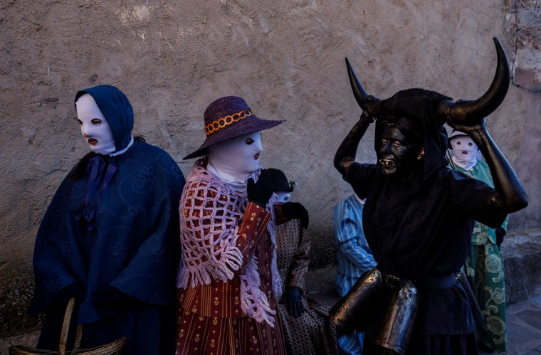 """Masked people dressed as """"Mascaritas"""" pose with others sporting horns on their heads and grease on their faces to represent """"Diablos de Luzon"""" (Luzon's devils) during the carnival in Luzon, near Guadalajara, on February 25, 2017. (CESAR MANSO/AFP/Getty Images)"""