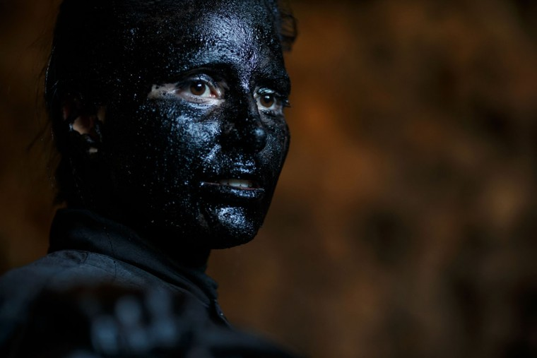 """A woman with grease on her face to represent """"Diablos de Luzon"""" (Luzon's devils) prepares during the carnival in Luzon, near Guadalajara, on February 25, 2017. (CESAR MANSO/AFP/Getty Images)"""