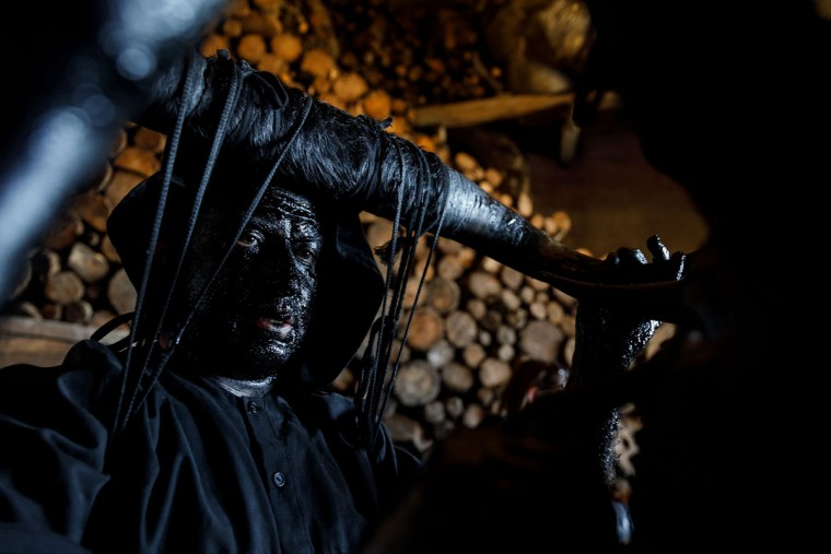 """A man sporting horns on his head and grease on his faces to represent """"Diablos de Luzon"""" (Luzon's devils) prepares during the carnival in Luzon, near Guadalajara, on February 25, 2017. (CESAR MANSO/AFP/Getty Images)"""