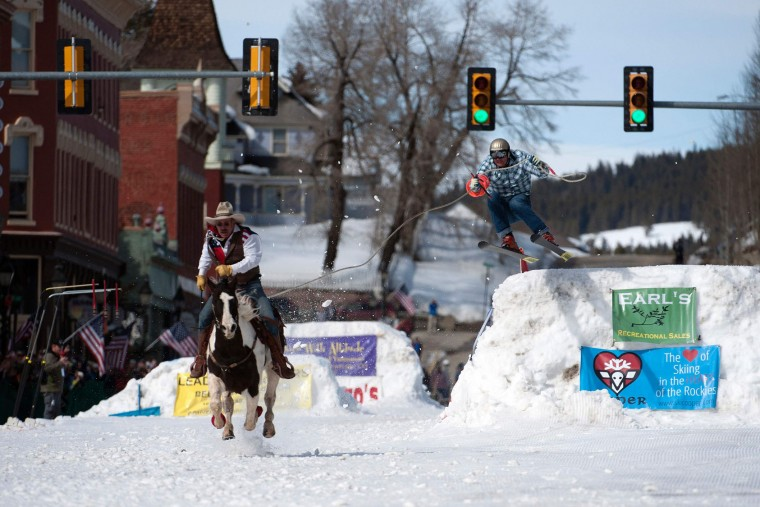 Rider Jeff Dahl races down Harrison Avenue while skier and son Greg Dahl airs out off the final jump of the Leadville skijoring course during the 68th annual Leadville Ski Joring weekend competition on Saturday, March 4, 2017 in Leadville, Colorado. Skijoring, which has its origins as a competitive sport in Scandinavia, has been adapted over the years to include a team made up of a rider and skier who must navigate jumps, slalom gates, and the spearing of rings for points. Leadville, with an elevation of 10,152 feet (3,094 m), the highest incorporated city in North America, has been hosting skijoring competitions since 1949. (Jason Connolly/AFP/Getty Images)