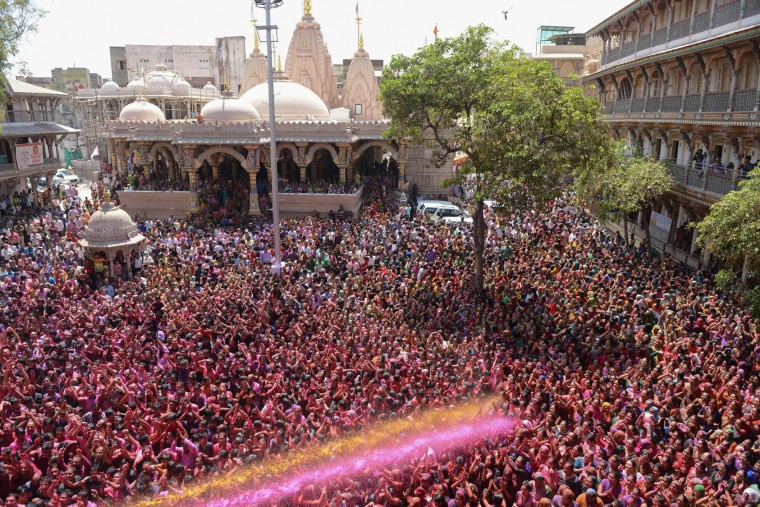 Indian Hindu devotees are sprayed with coloured water by heir to the Kalupur Swaminarayan Temple Lalji Maharaj Shri Vrajendraprasdaji Maharaj as they celebrate the Holi festival at the Swaminarayan Temple in Ahmedabad on March 13, 2017. The Hindu festival of Holi, or the 'Festival of Colours' heralds the arrival of spring and the end of winter. (Sam Panthaky/AFP/Getty Images)