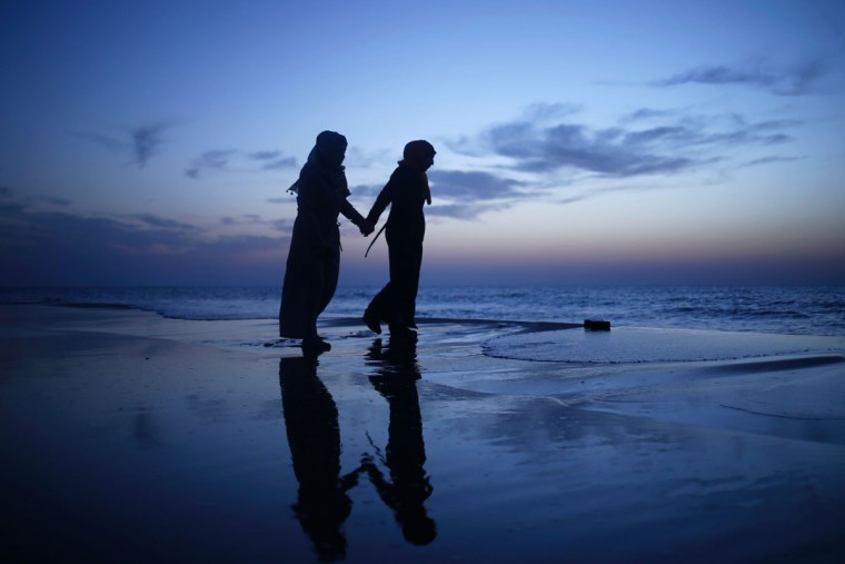 Palestinian girls walk holding hands at sunset on the beach in Gaza City as people around the world mark International Women's Day on March 8, 2017. (MOHAMMED ABED/AFP/Getty Images)