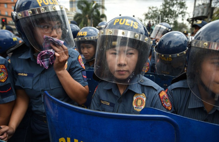 Police women holding truncheons stand guard as women's group Gabriela hold a rally to celebrate International Women's Day near the US embassy in Manila on March 8, 2017. (TED ALJIBE/AFP/Getty Images)