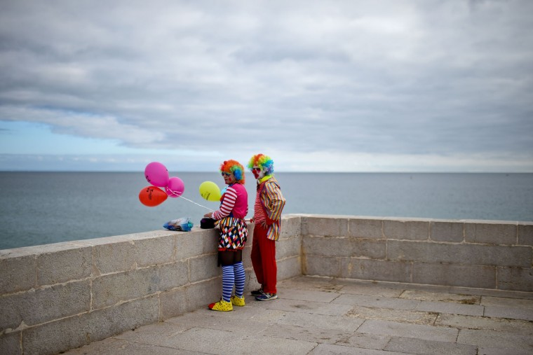 A couple dressed as clowns stands near the beach during the Carnival Clown's Parade at Sesimbra village on February 27, 2017. (Patricia de Melo Moreira/AFP/Getty Images)
