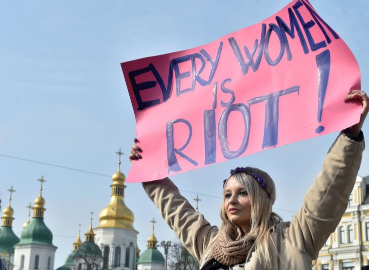 A woman carries a sign during a march as part of International Women's Day. (SERGEI SUPINSKY/AFP/Getty Images)