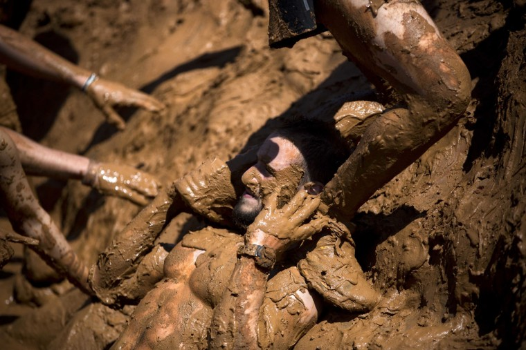 People take part in the Mud Day race, a 13 kilometer obstacle course in Tel Aviv, Israel, Friday, March 24, 2017. (AP Photo/Oded Balilty)