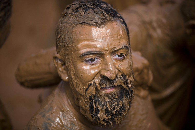 A man takes part in the Mud Day race, a 13 kilometer obstacle course in Tel Aviv, Israel, Friday, March 24, 2017. (AP Photo/Oded Balilty)