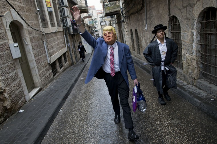 An ultra-Orthodox Jewish man wears U.S. President Donald Trump's mask during the Purim festival in Mea Shearim ultra-Orthodox neighborhood in Jerusalem, Monday, March 13, 2017. The Jewish holiday of Purim celebrates the Jews' salvation from genocide in ancient Persia, as recounted in the Scroll of Esther. (AP Photo/Oded Balilty)