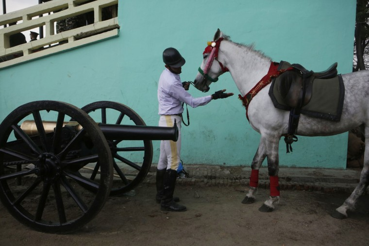 A Nepalese Army soldier gets his horse ready for the Ghode Jatra festival, an annual horse festival in Kathmandu, Nepal, Monday, March 27, 2017. According to legend, the festival is held to celebrate the victory over a demon named Tundi and people believe that the clamor of horses' hooves during the festival keeps the demon's spirit away. (AP Photo/Niranjan Shrestha)