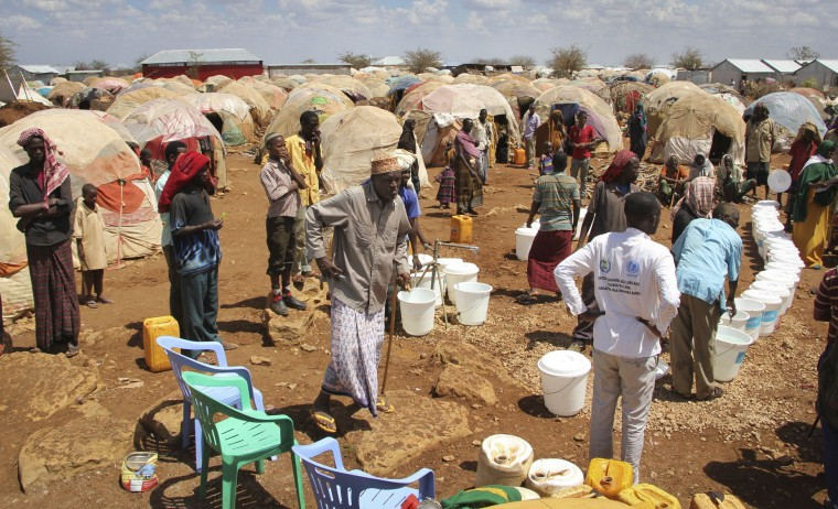 In this photo taken Saturday, March 25, 2017, newly displaced Somalis gather next to a water point at a camp in Baidoa, Somalia. Somalia's drought is threatening 3 million lives according to the U.N. and in recent months aid agencies have been scaling up their efforts but say more support is urgently needed to prevent the crisis from worsening. (AP Photo/Farah Abdi Warsameh)