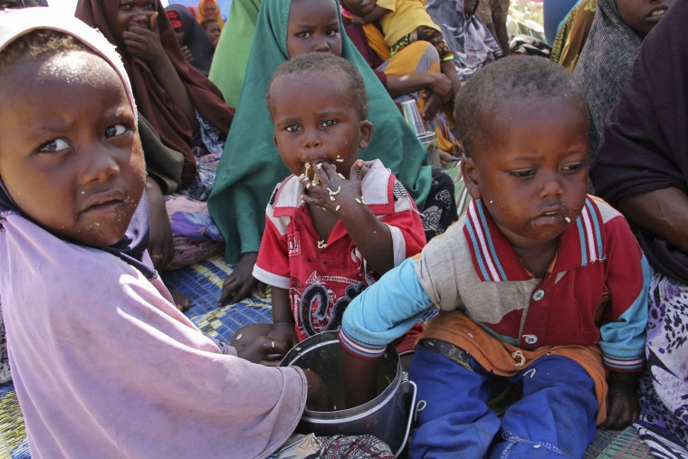 Newly displaced children eat food as they sit on the ground, just outside of Mogadishu, in Somalia, Monday, March, 27, 2017. Somalia's drought is threatening 3 million lives, according to the U.N. In recent months, aid agencies have been scaling up their efforts but they say said more support is urgently needed to prevent the crisis from worsening. (AP Photo/Farah Abdi Warsameh)