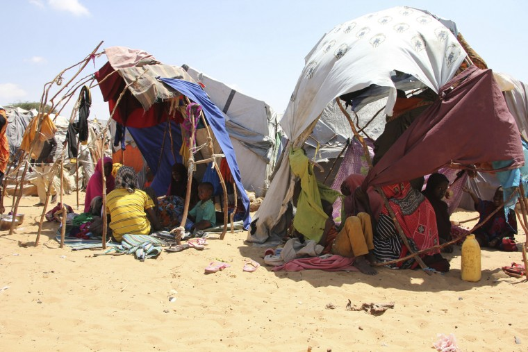 Newly displaced Somali women and children sit in makeshift shelters in a camp outside of Mogadishu, Somalia, Monday, March, 27, 2017. Somalia's drought is threatening 3 million lives according to the U.N. and in recent months aid agencies have been scaling up their efforts but say more support is urgently needed to prevent the crisis from worsening. (AP Photo/Farah Abdi Warsameh)