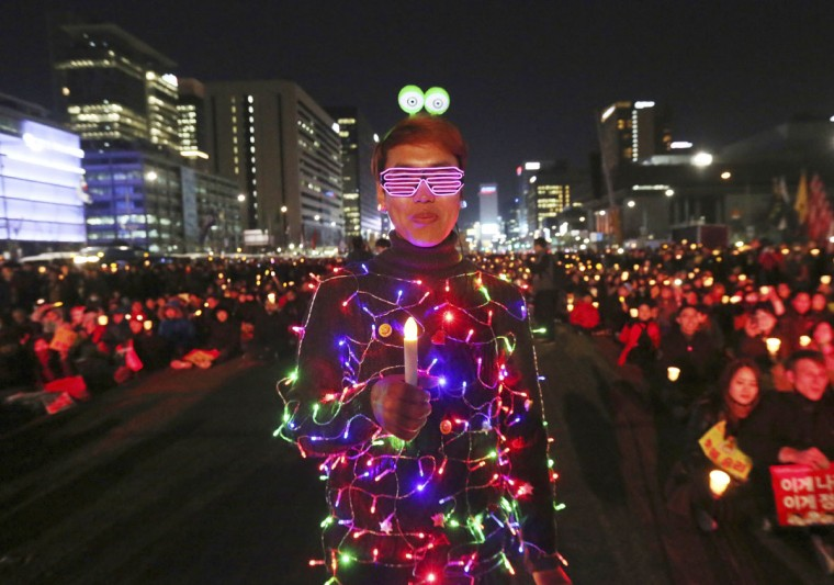 A protester wearing electric lights attached to his clothing attends a rally calling for impeached President Park Geun-hye's arrest in Seoul, South Korea, Friday, March 10, 2017. The Constitutional Court removed impeached President Park Geun-hye from office in a unanimous ruling Friday over a corruption scandal that has plunged the country into political turmoil and worsened an already-serious national divide. (AP Photo/Ahn Young-joon)