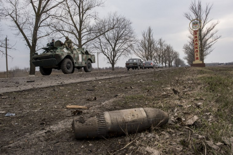 A Ukrainian APC rides past a shell on a road after a massive fire at a military depot in Balaklia, Ukraine, Friday, March 24, 2017. About 20,000 people were evacuated in Kharkiv region near the border with Russia when the fire broke out Thursday at one of Ukraine's largest military arsenals, which held huge stocks of large-caliber artillery rounds. (AP Photo/Evgeniy Maloletka)