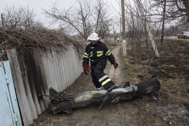 A Ukrainian emergency employee steps over a part of a missile after a massive fire at a military depot in Balaklia, Ukraine, Friday, March 24, 2017. About 20,000 people were evacuated in Kharkiv region near the border with Russia when the fire broke out Thursday at one of Ukraine's largest military arsenals, which held huge stocks of large-caliber artillery rounds. (AP Photo/Evgeniy Maloletka)