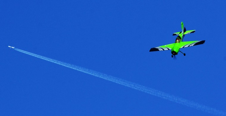 A model airplane flown by a member of the Harford County Radio Control Modelers (HCRCM) flies at a much lower altitude than a passing jetliner leading its contrail thousands of feet overhead. (Kenneth K. Lam/Baltimore Sun)