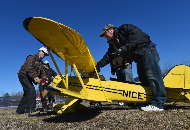Doug Brackens, right, helps fellow member Arthur Pearce start his 1/3 scale YMF Waco RC model airplane. (Kenneth K. Lam/Baltimore Sun)
