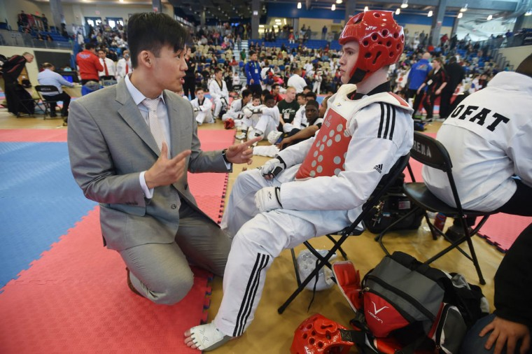 "Yong Seong ""CJ"" Chang, left, instructs student Kyle Powers (red), of Kingsville, in between rounds during sparring contest. Over 500 competed in the First Maryland Governor's Cup Taekwondo Championship hosted by the Maryland State Taekwondo Association at the APGFCU Arena Harford Community College. Competitors, ages from 3 to over 60 and from as far as Maine, competed in forms, board breaking and sparring in a full day of contests. All proceeds from the championship will be donated to the Children's Cancer Foundation (CCF). (Kenneth K. Lam/The Baltimore Sun)"
