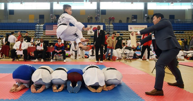 Brandon Santiago, 13, of Bel Air, jumps over six of his friends to break a board during competition. Over 500 competed in the First Maryland Governor's Cup Taekwondo Championship hosted by the Maryland State Taekwondo Association at the APGFCU Arena Harford Community College. Competitors, ages from 3 to over 60 and from as far as Maine, competed in forms, board breaking and sparring in a full day of contests. All proceeds from the championship will be donated to the Children's Cancer Foundation (CCF). (Kenneth K. Lam/The Baltimore Sun)