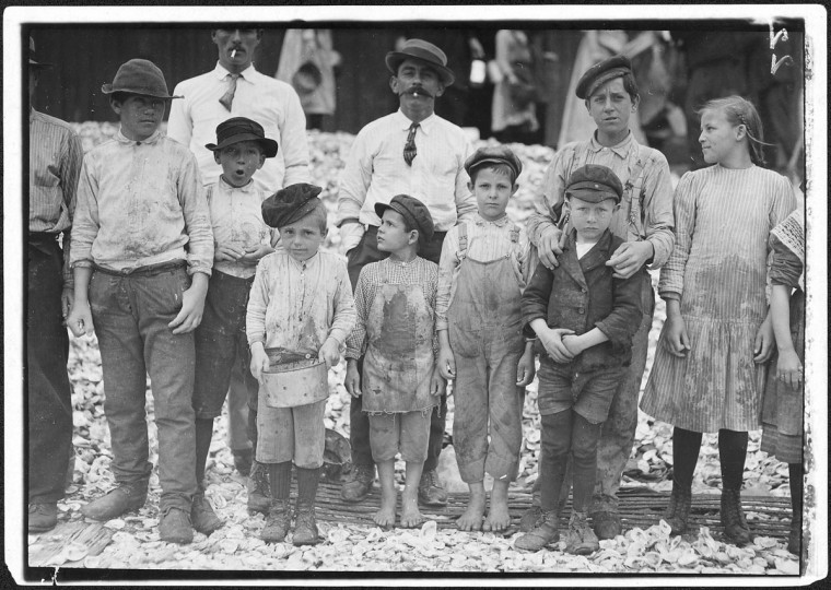 Original Caption: All these are shrimp pickers. Youngest in photo are 5 and 8 years old. Biloxi, Miss, February 1911. (Lewis Hine/Photo courtesy of NARA)