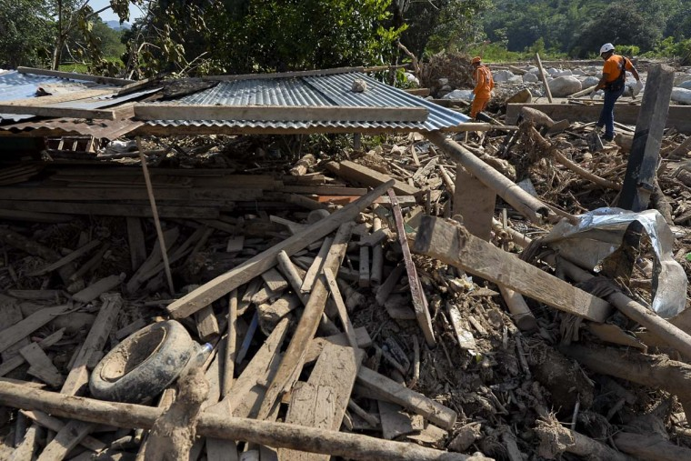 Colombian Civil Defense workers walk next to a house destroyed by mudslides caused by heavy rains in Mocoa, Putumayo department, Colombia on April 5, 2017. A state of economic emergency has been declared in the town of Mocoa in southern Colombia, after mudslides left more than 290 people dead. And local officials urged the government to dispatch more police and troops to secure the region and prevent the looting of abandoned homes. (LUIS ROBAYO/AFP/Getty Images)