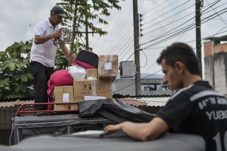 Men load boxes onto a public transport vehicle leaving Mocoa, Putumayo department, Colombia, on April 5, 2017, affected by a mudslides caused by heavy rains. A state of economic emergency has been declared in the town of Mocoa in southern Colombia, after mudslides left more than 290 people dead. And local officials urged the government to dispatch more police and troops to secure the region and prevent the looting of abandoned homes, while some residents have decided to leave for a while for fear of epidemics that could be caused by the natural disaster. (LUIS ROBAYO/AFP/Getty Images)
