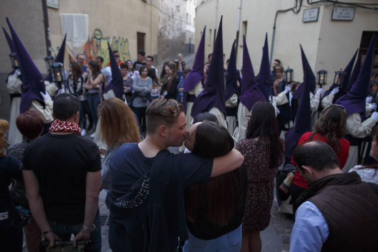 A couple kiss each other as penitents from the Jesus del Via Crucis (Jesus of the Way of the Cross) brotherhood take part in a procession on April 11, 2017 in Zamora, Spain. Spain celebrates holy week before Easter with processions in most Spanish towns and villages. (Photo by Pablo Blazquez Dominguez/Getty Images)