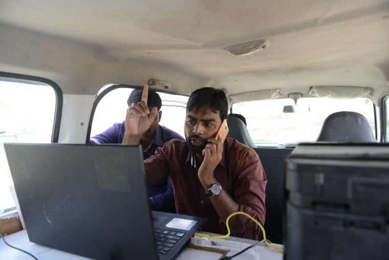 This picture taken on April 7, 2017 shows Rahul Chaudhry (right), project co-ordinator of the Digital Empowerment Foundation, working in an Internet-connected van used in the 'Zero Connect' programme at a tent school workshop for a group of children of salt pan workers in the Little Rann of Kutch (LRK) region of Gujarat, near Dhrangadhra, some 160km west of Ahmedabad. The children of Indian salt pan workers, drawn from the Agariya community in Gujarat state, accompany their parents in the remote and arid Little Rann of Kutch (LRK) region for nearly eight months of the year during the salt farming season. The 'Zero Connect' initiative provides basic education for the children in a joint initiative by the Agaria Heet Rakshak Manch, Digital Empowerment Foundation, Internet Society and Wireless for Communities groups. The initiative runs mobile workshops for the children, providing online access and education materials. (SAM PANTHAKY/AFP/Getty Images)