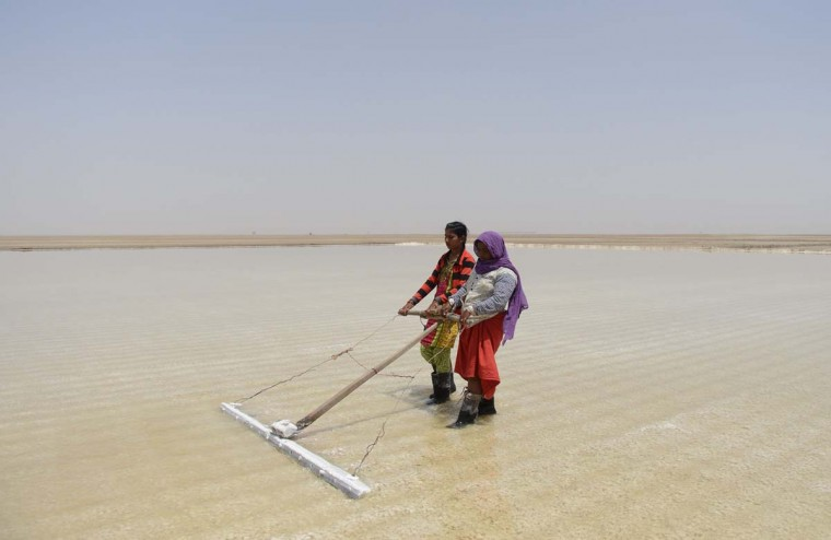 This picture taken on April 8, 2017 shows Indian salt pan worker Puja Ganeshbhai Muladiya (left) along with her mother Devuben working in a salt pan in the Little Rann of Kutch (LRK) region of Gujarat some 180km west of Ahmedabad. Indian salt pan workers of the Agariya community in Gujarat work in the remote and arid Little Rann of Kutch (LRK) region for nearly eight months of the year during the salt farming season. India is ranked third in gross amount of salt produced in the world, behind China and the United States, and the western state of Gujarat accounts for 77 percent of India's production. (SAM PANTHAKY/AFP/Getty Images)