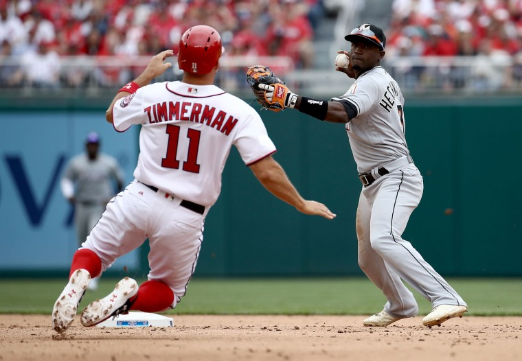 Adnely Hechavaria #3 of the Miami Marlins turns a double play as Ryan Zimmerma #11 of the Washington Nationals slides into second base in the Opening Day game against the Miami Marlins on April 3, 2017 at Nationals Park in Washington, DC. Washington won the game 4-2. (Photo by Win McNamee/Getty Images)