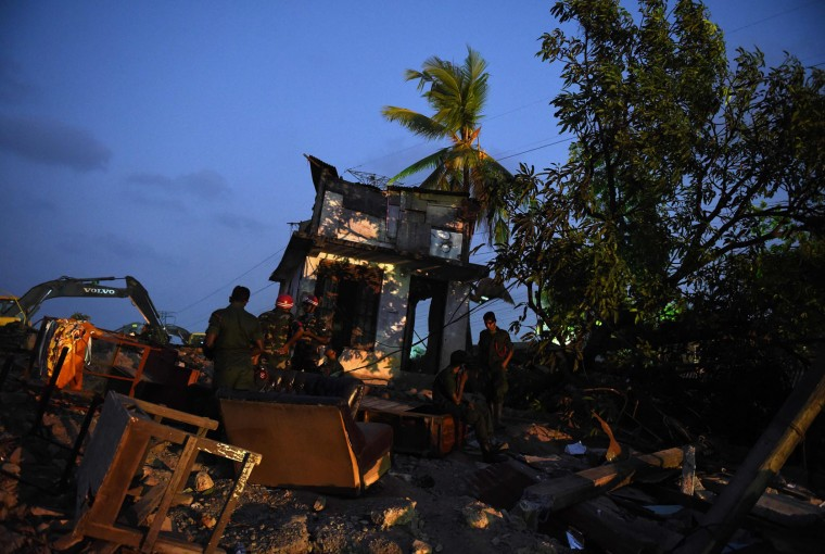Sri Lankan military personnel stand among damaged homes at the site of a collapsed garbage dump in Colombo on April 16, 2017. Hopes of finding anyone alive under a collapsed mountain of garbage in Sri Lanka's capital faded as the death toll reached 23 with another six reported missing, police said. Hundreds of soldiers, backed by heavy earth moving equipment were digging through the rubbish and the wreckage of some 145 homes that were destroyed when a side of the 300-foot (90-metre) high dump crashed on April 14. (Ishara S. Kodikara/AFP/Getty Images)