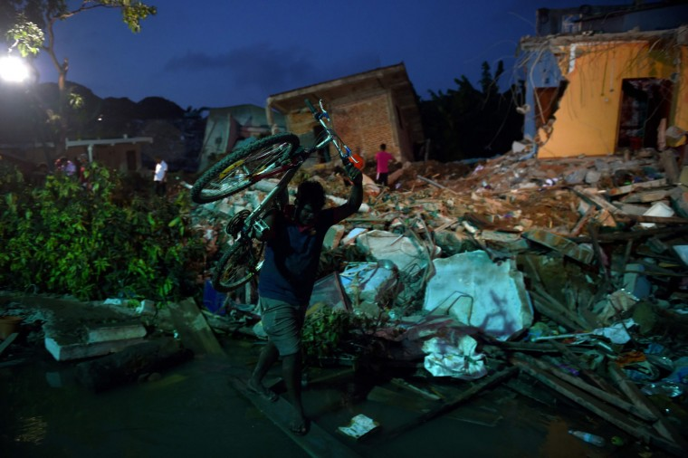 A Sri Lankan resident salvages a bicycle from among damaged homes at the site of a collapsed garbage dump in Colombo on April 16, 2017. Hopes of finding anyone alive under a collapsed mountain of garbage in Sri Lanka's capital faded as the death toll reached 23 with another six reported missing, police said. Hundreds of soldiers, backed by heavy earth moving equipment were digging through the rubbish and the wreckage of some 145 homes that were destroyed when a side of the 300-foot (90-metre) high dump crashed on April 14. (Ishara S. Kodikara/AFP/Getty Images)