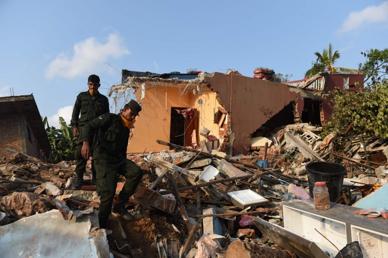 Sri Lankan military personnel walk among damaged homes at the site of a collapsed garbage dump in Colombo on April 16, 2017. Hopes of finding anyone alive under a collapsed mountain of garbage in Sri Lanka's capital faded as the death toll reached 23 with another six reported missing, police said. Hundreds of soldiers, backed by heavy earth moving equipment were digging through the rubbish and the wreckage of some 145 homes that were destroyed when a side of the 300-foot (90-metre) high dump crashed on April 14. (Ishara S. Kodikara/AFP/Getty Images)