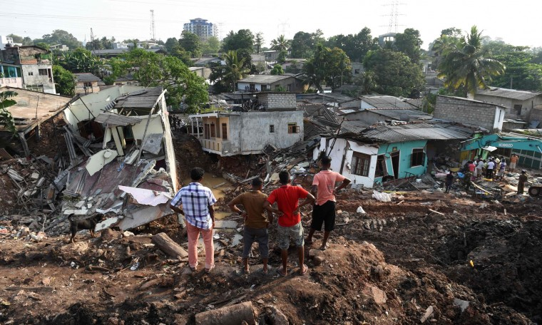 Sri Lankan residents survey damaged homes at the site of a collapsed garbage dump in Colombo on April 16, 2017. Hopes of finding anyone alive under a collapsed mountain of garbage in Sri Lanka's capital faded as the death toll reached 23 with another six reported missing, police said. Hundreds of soldiers, backed by heavy earth moving equipment were digging through the rubbish and the wreckage of some 145 homes that were destroyed when a side of the 300-foot (90-metre) high dump crashed on April 14. (Ishara S. Kodikara/AFP/Getty Images)