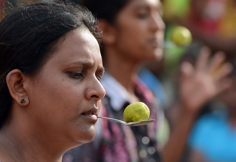 Sri Lankan participants use a lemon and spoon at Piliyandala near Colombo on April 14, 2017, as they take part in traditional festival games held to celebrate to mark the Sinhala and Tamil New Year. The new year which is common to both majority Sinhalese and minority Tamils dawned on April 14, but celebrations can go on for weeks. (Lakruwan Wanniarachchi/AFP/Getty Images)