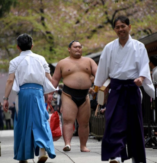 A sumo wrestler walks past spectators in a compound of Yasukuni Shrine in Tokyo on April 17, 2017. Sumo's top wrestlers took part in an annual one-day exhibition for thousands of spectators within the shrine's precincts. (TOSHIFUMI KITAMURA/AFP/Getty Images)